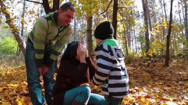 Happy Young Family Enjoying Autumn Time In The Forest