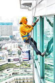 Painters high building condo outdoors sprinkle with rope safe sure in bangkok thailand.