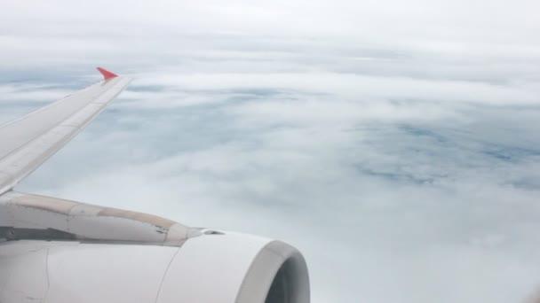 Flugzeugflügel und Triebwerk mit Wolke und Himmel