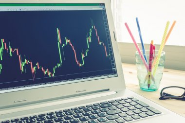 Stock or Forex Graph in Laptop Screen on Left View on Blue Vintage Style