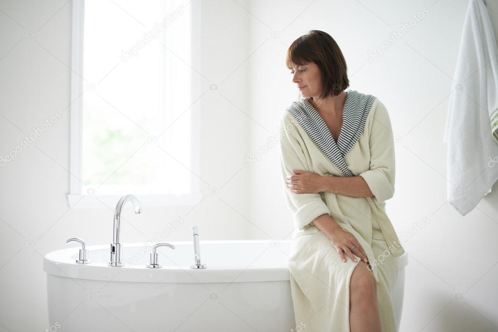 Serena donna matura seduto da una vasca da bagno u foto stock