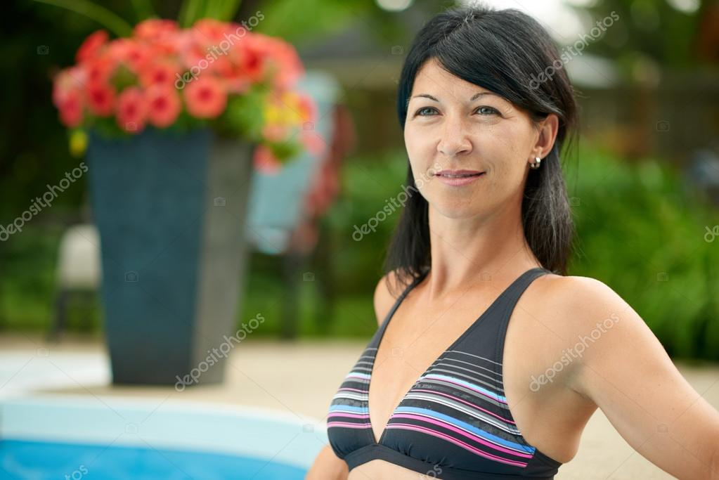 Mature woman swimming in a blue water pool