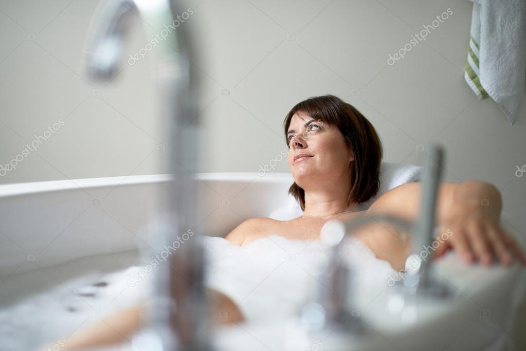 Serene mature woman looking away in a bathtub u stock photo