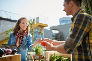 Friendly woman tending an organic vegetable stall at a farmers market and selling fresh vegetables from the rooftop garden