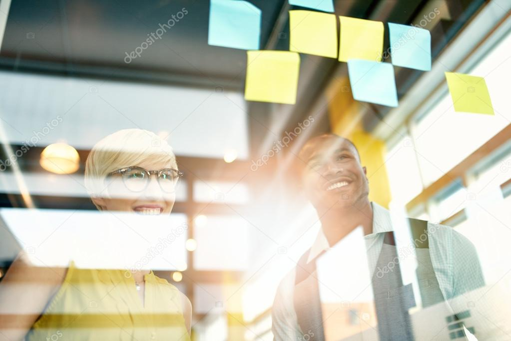 Two creative millenial small business owners working on social media strategy brainstorming using adhesive notes in windows