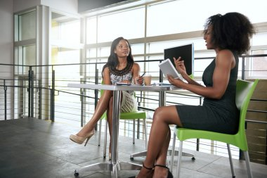 Two african american women discussing ideas using a tablet and computer