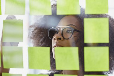 Portrait of a business woman with an afro behind sticky notes in bright glass office