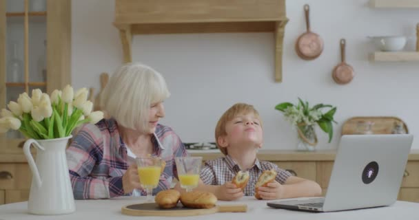 Grandmother and grandson eating buns and drinking orange juice sitting at dining table at kitchen. Family having fun enjoying homemade pastry.