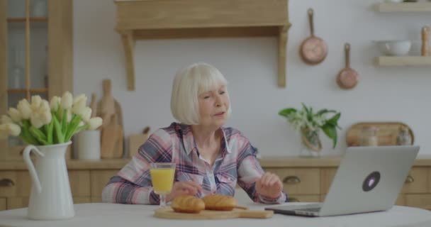 Senior woman talking online by laptop sitting at wooden kitchen. Smiling elderly woman having online conversation. Granny stays at home and chats with relatives online. 70s woman drinks orange juice.