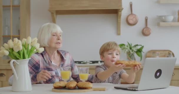 Grandmother and grandson eating buns and drinking orange juice sitting at dining table at kitchen. Family enjoys homemade pastry while talking online by laptop.