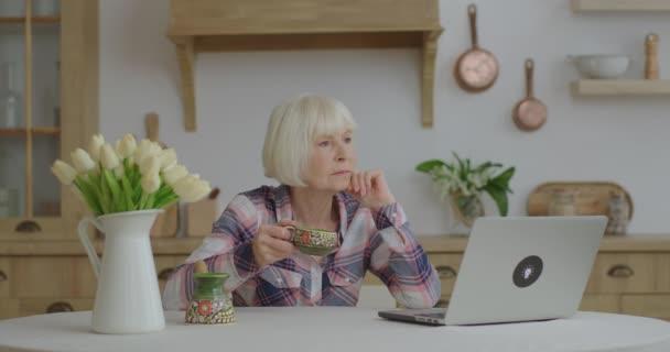 Seniorin trinkt Kaffee und unterhält sich online per Laptop in Holzküche. Ältere Frau bleibt allein zu Hause und genießt Kaffee.