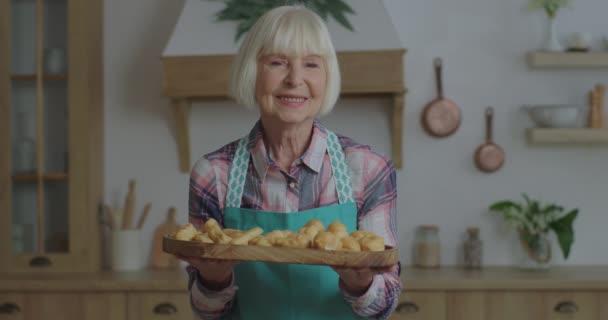 Seniorin blonde Frau hält Teller mit Backwaren wie hausgemachte Eclairs, Croissants, Brötchen. Ältere Frau steht lächelnd in der Küche und blickt in die Kamera.
