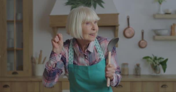 Fröhliche ältere blonde Frau, die in Geschirr singt wie ein Mikrofon in der Holzküche. Ältere Frauen tanzen emotional und bleiben zu Hause. Schaufel als Mikrofon.