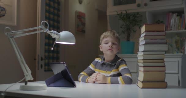 Dítě ve školce vybírá papírové knihy nebo tabletový počítač s očima. Elektronická nebo papírová volba učení. Zmatené dítě s gadgetem a knihami.