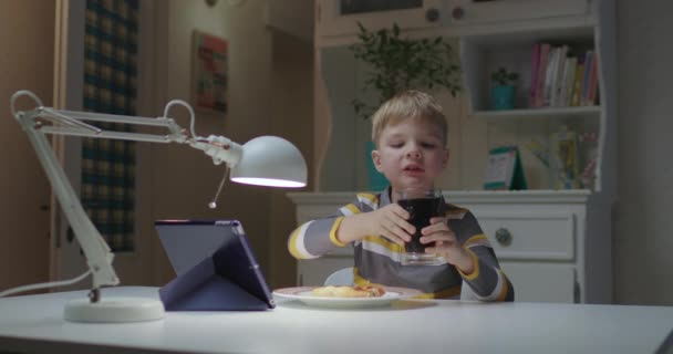 Preschool boy eating pizza and watching tablet computer online at home. Kid enjoy eating pizza and drinking cola.