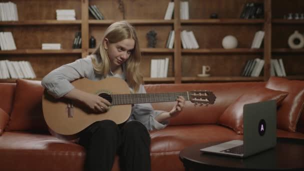 A húszas éveiben járó nő gitározni tanul, laptopot bámul otthon a kanapén. Online zenei tanulás koncepciója. Zenehallgató akusztikus gitáron játszik.