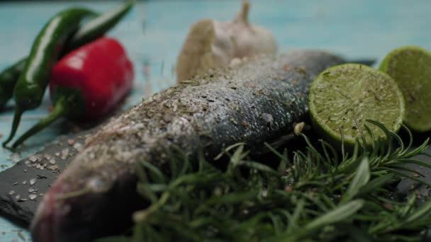 Nalít bylinky na čerstvé ryby. Příprava na vaření mořčáka evropského na grilu. Vaření ryb s kořením a solí. Dekorovaná rybí mísa. Zblízka padajícího koření.