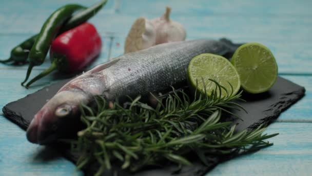 Pouring salt on fresh fish. Preparation for cooking sea bass fish on grill. Cooking fish with spices and salt. Decorated fish dish.