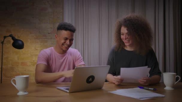 Junges gemischtes Paar legte gemeinsam Online-Prüfung ab. Happy millennial afroamerikanische Studentin gibt High Five an Freundin für erfolgreiche Prüfung durch das Internet.
