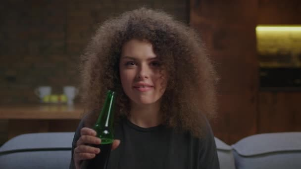 Millennial female soccer fan watching game on couch with beer. Woman celebrates victory goal of favorite team in front of tv. Close up of young curly woman drinking beer.