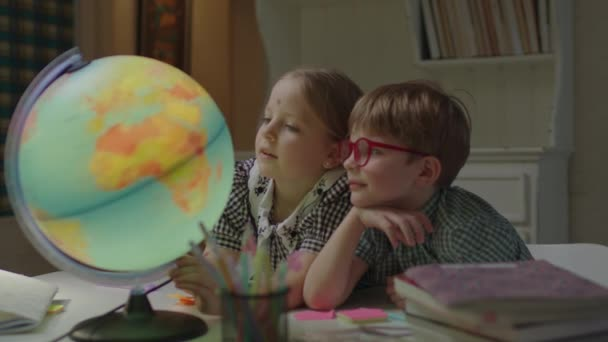 Schoolgirl and schoolboy studying Earth globe on the desk with textbooks. Siblings learning at home together. Children exploring Earth planet with globe.