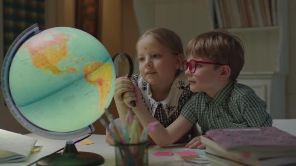 Két gyerek tanulmányozza a Föld gömbjét nagyítóval. A testvérek együtt tanulnak otthon. Lány és fiú felfedező Föld bolygó a világon a loupe.