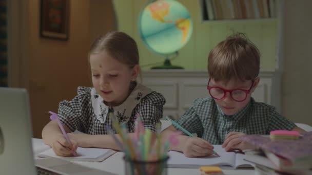 Fiú és lány írnak tollal, laptopot néznek. Két testvér online órát tart otthon az asztalnál. Gyerekek távoli tanulás otthonról