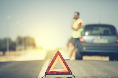Emergency triangle in the middle of the road. Man and car in the