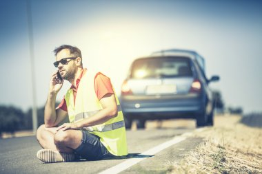 Man sitting on the road, talking by phone after a car breakdown.