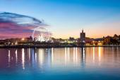 Sunset cityscape with ferris wheel in motion. Malaga city, Spain