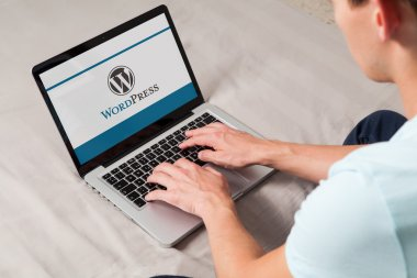 MALAGA, SPAIN - NOVEMBER 10, 2015: Wordpress brand logo on computer screen. Man typing on the keyboard. WordPress is a free and open-source blogging tool and a content management system (CMS).