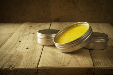 Open glass pot with honey moisturizer isolated
