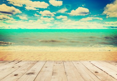 Wood table sand beach sea and in sky clouds with vintage tone.