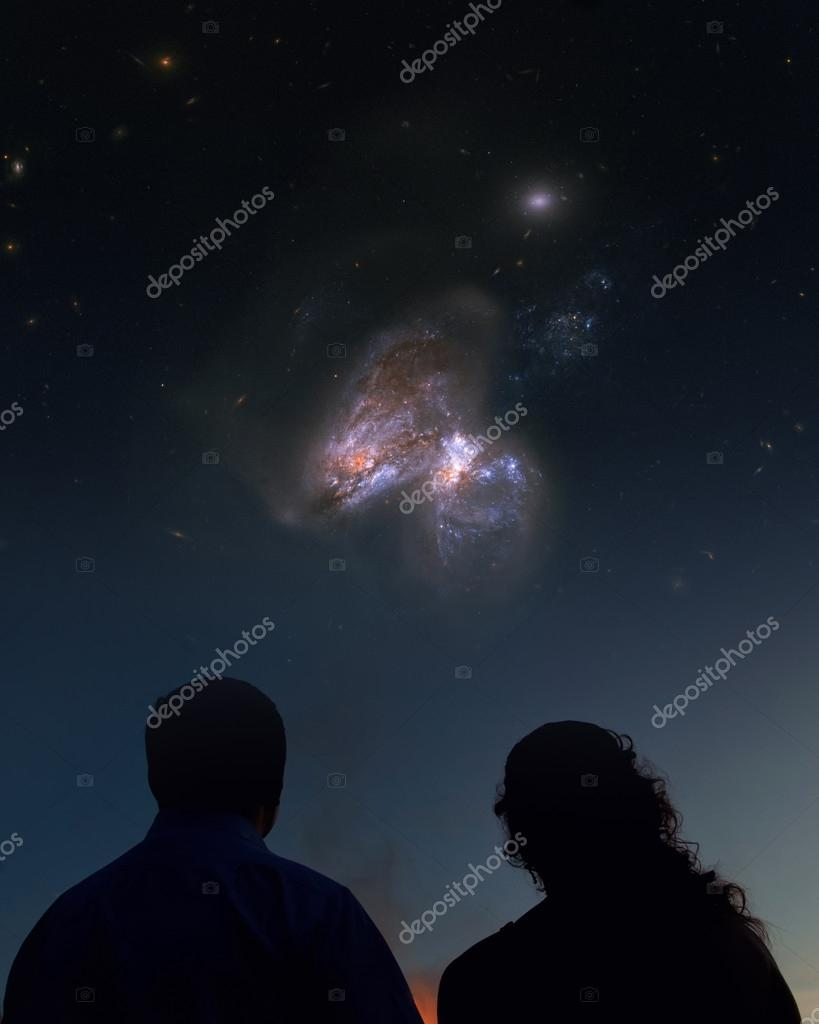 Silhouettes of couple looking at stars. Starry night sky with colorful galaxies, astronomical background with place for your text.Elements of this image furnished by NASA.
