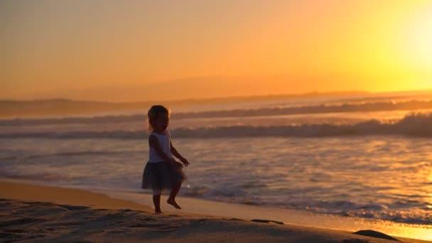 Roztomilé dívky běží k matce na pláži se zbraněmi. Šťastnou rodinnou zábavu na pobřeží. Máma a dcera tancují a hrají si při západu slunce. Vlny za úsvitu dítě běží podél břehu s rodičem.