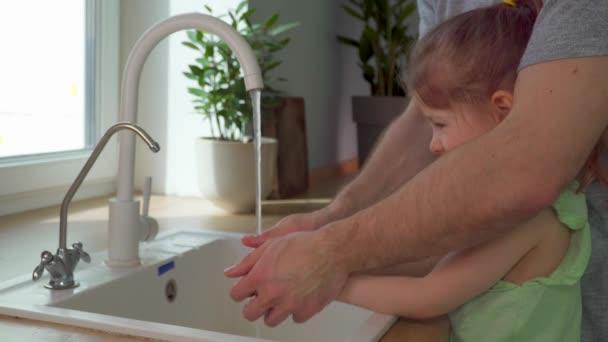Uč děti mýt si ruce mýdlem. Táta pomáhá dceři s osobní hygienou. muž a dívka si hrají s vodou doma v kuchyni. Ochranné viry a mikrobi s antibakteriálním gelem. Rodinná zábava společně.