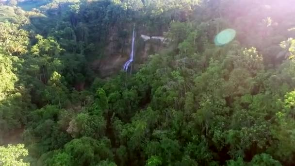 Flying toward waterfall over tropical forest. Drone aerial shot