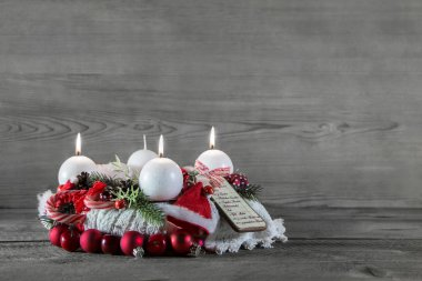 Advent crown with three candles in red and white on grey wooden