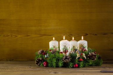 Rustic  advent wreath or crown with four burning white candles.