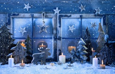 Outdoor christmas window decoration in blue with wood and candle
