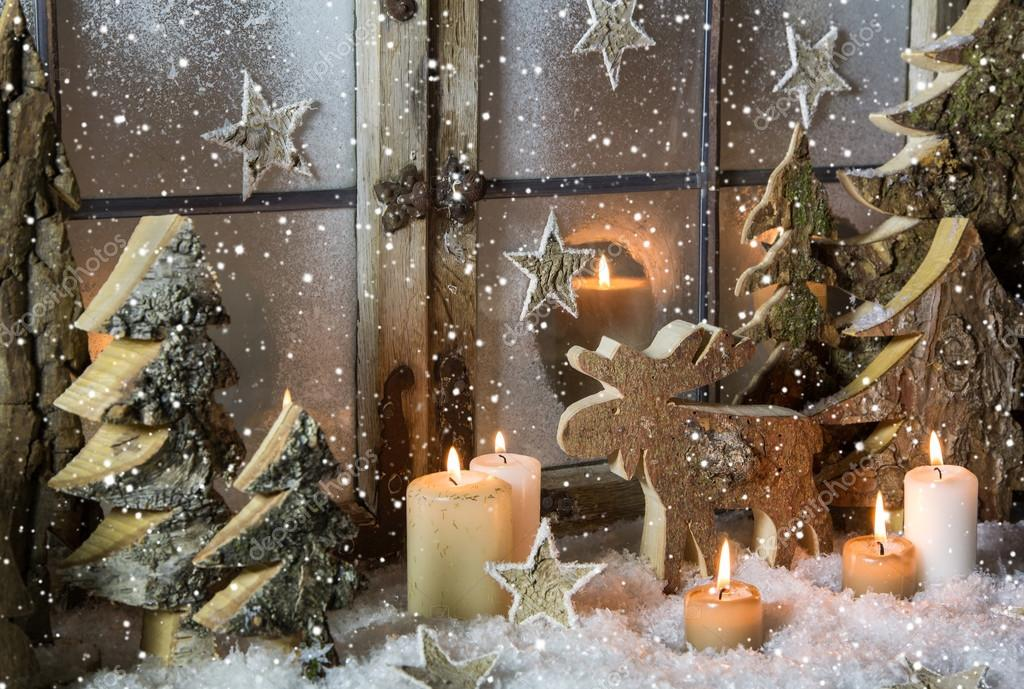 Natural christmas window decoration of wood with snow.