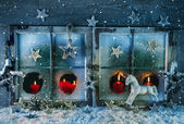 Fotografie Atmospheric christmas window with red candles outdoor with snow.