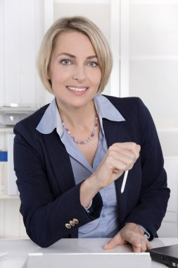 Attractive middle aged woman in business outfit sitting in her o