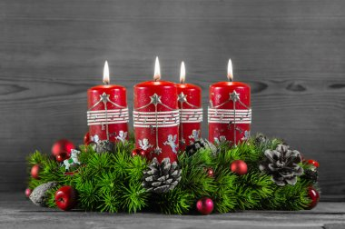 Advent wreath or crown with four red candles on wooden backgroun