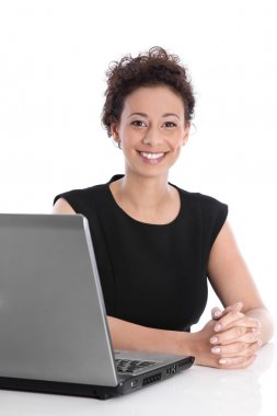 Happy young business woman sitting at desk with laptop.