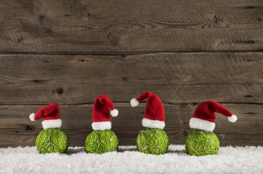 Funny christmas background with green balls and santa hats on wo