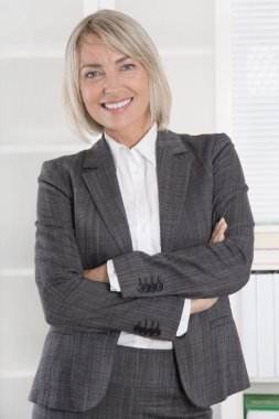 Attractive smiling middle aged businesswoman in portrait wearing