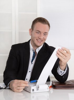 Happy entrepreneur looking at paper roll: concept for increasing