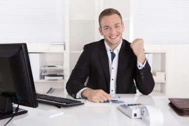 Successful young businessman proud of his success and cheering i