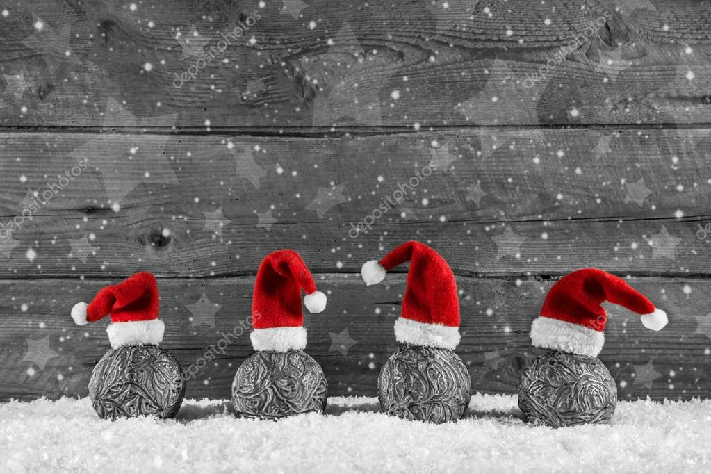 Grey festive wooden christmas background with four santa hats on